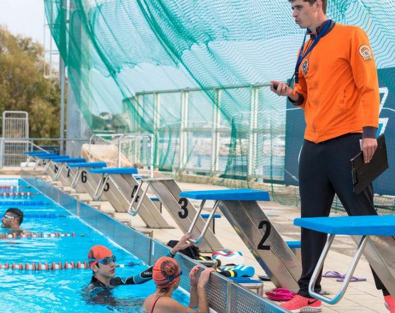 Тренер по плаванью работает с ребятами
